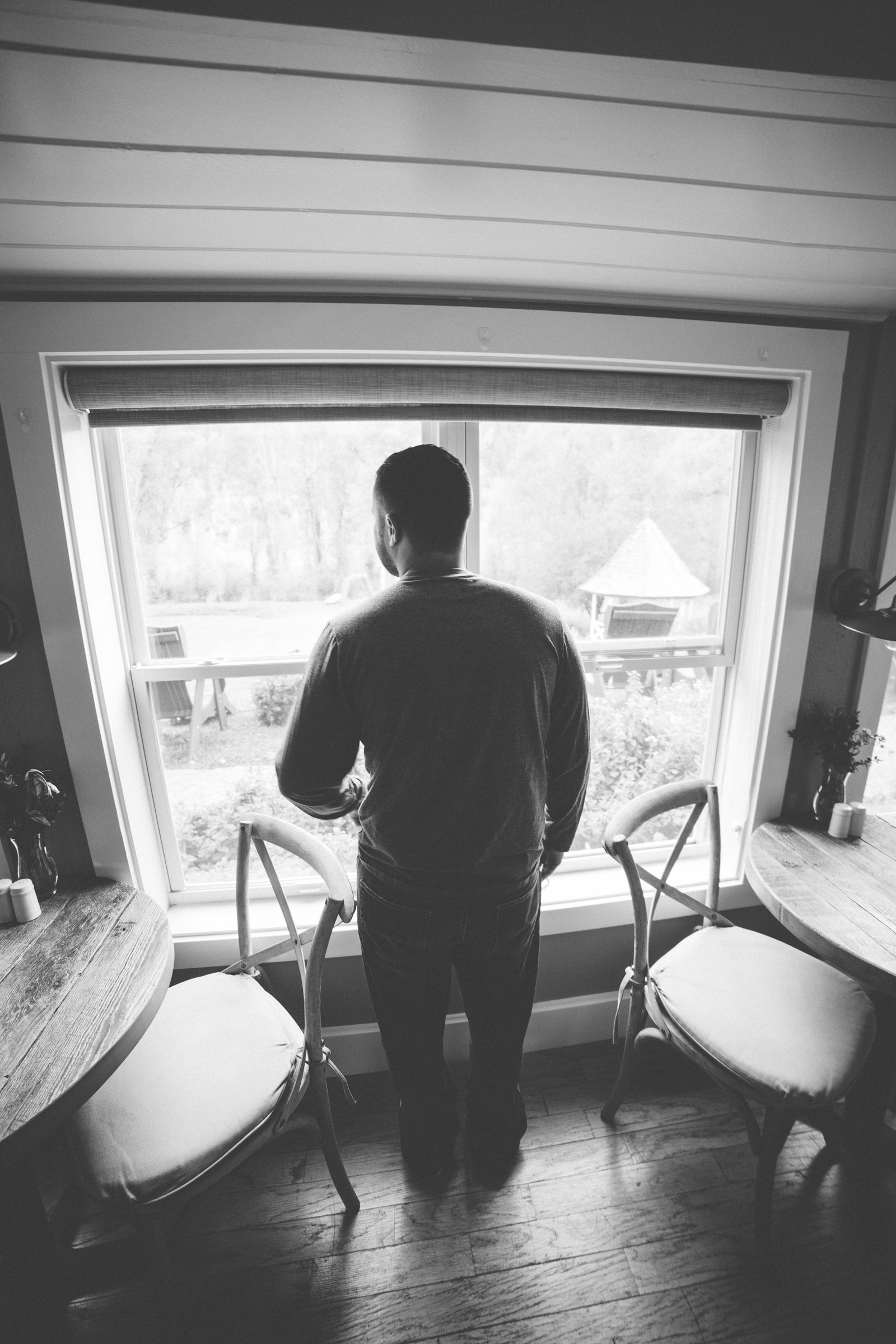 groom looking out window before ceremony in black and white image