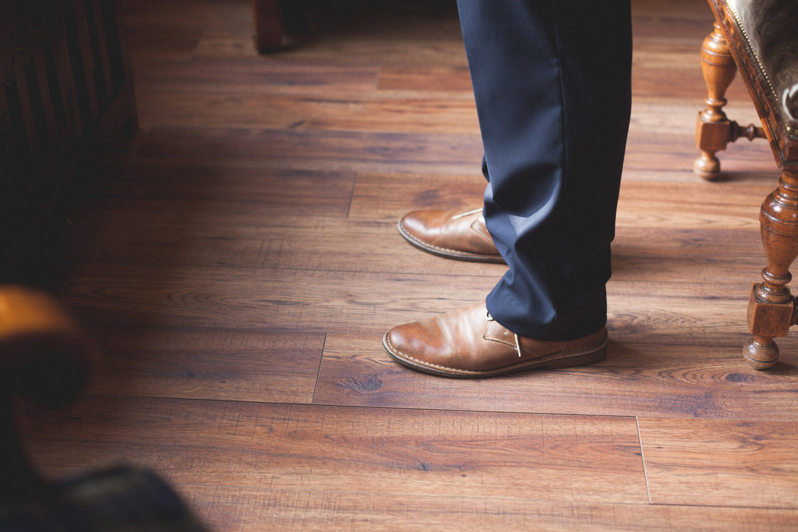 image of groom shoes against wood floor