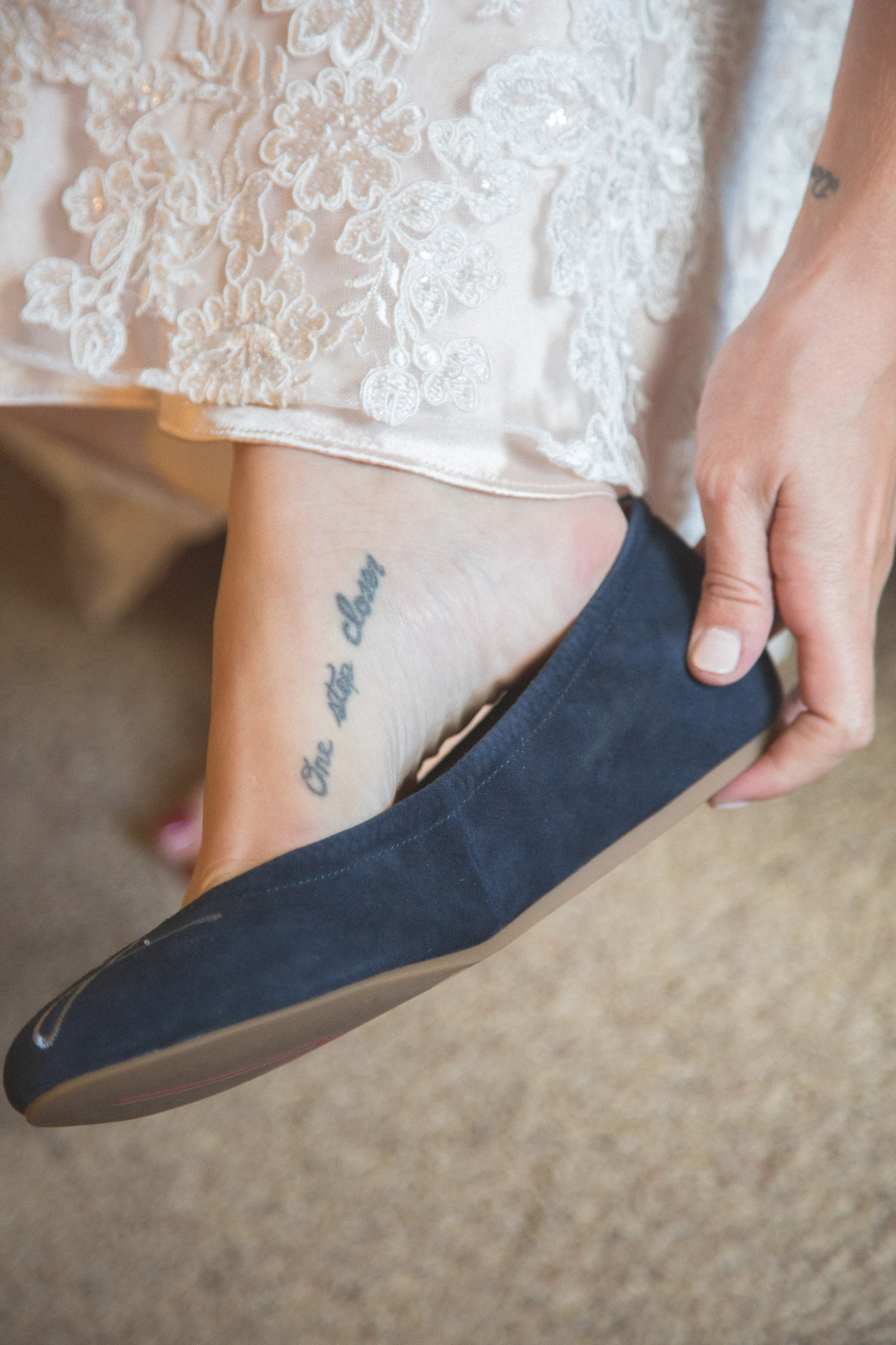 bride puting shoes on before elopment wedding ceremony