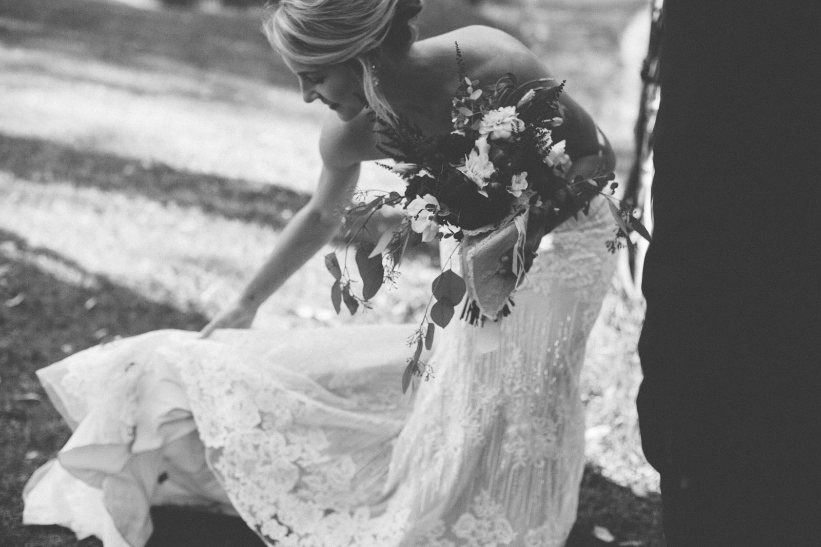 bride picking up her dress in aisle at grooms feet