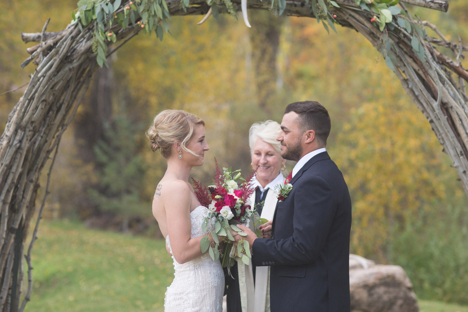 bride and groom smiling at each other during private elopement wedding ceremony at durango co
