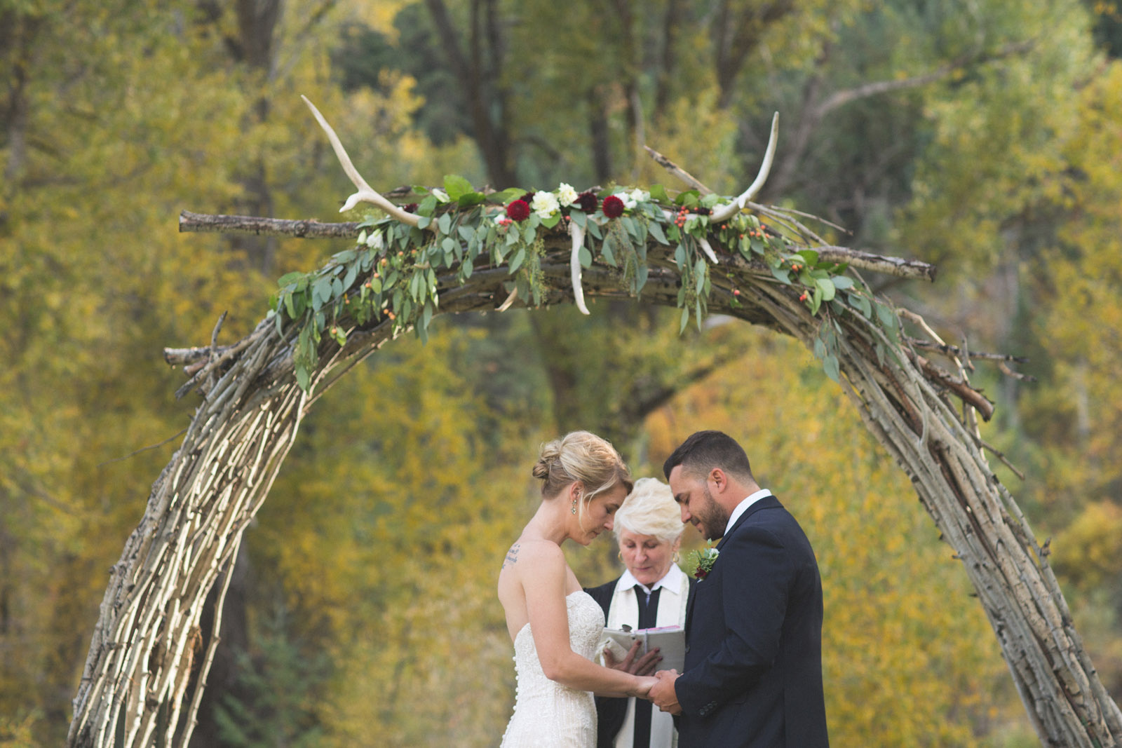 bride and groom praying during private elopement wedding ceremony in durango co forest