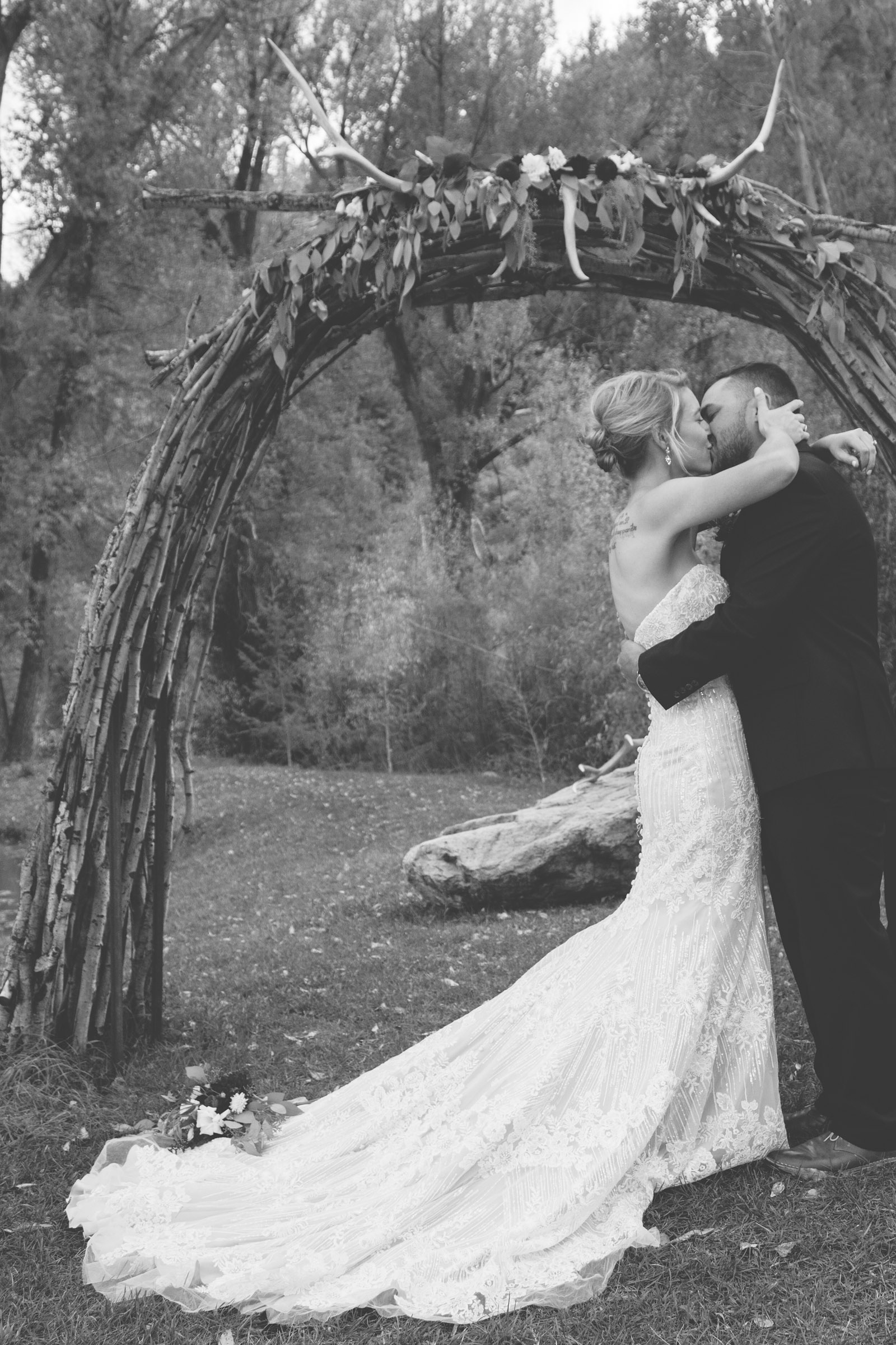 bride and groom first kiss during private elopement wedding ceremony in durango co forest